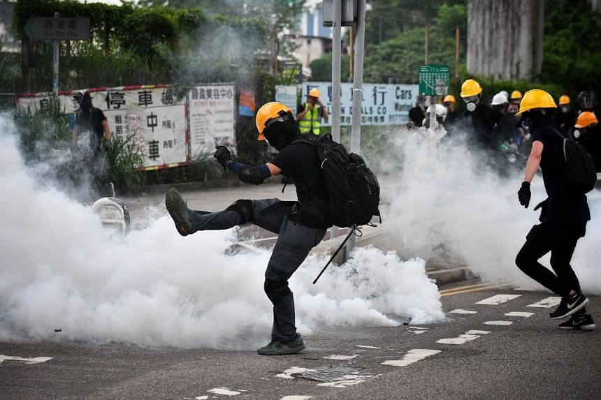 Protesters trying to kick away tear gas grenades during a confrontation with police in Yuen Long on July 27, 2019.