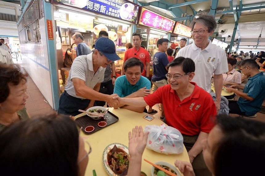DPM Heng Swee Keat (in red), together with Minister for Trade and Industry Chan Chun Sing (in blue) and East Coast GRC MP Lim Swee Say (right) greeting residents during a community visit in Bedok on July 27, 2019.