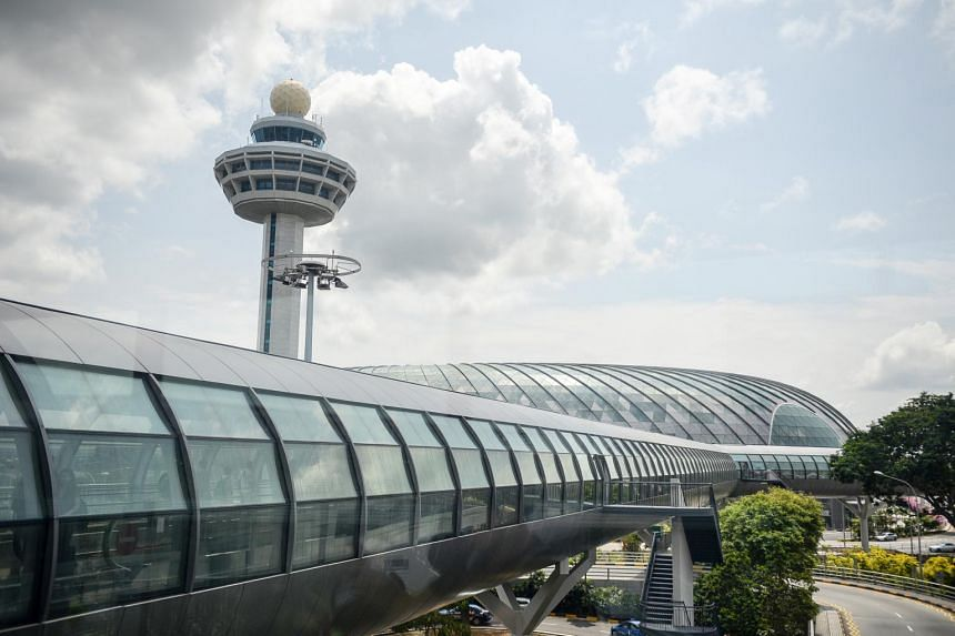 The glass walkway leading towards Jewel Changi Airport and the iconic Changi Airport control tower.