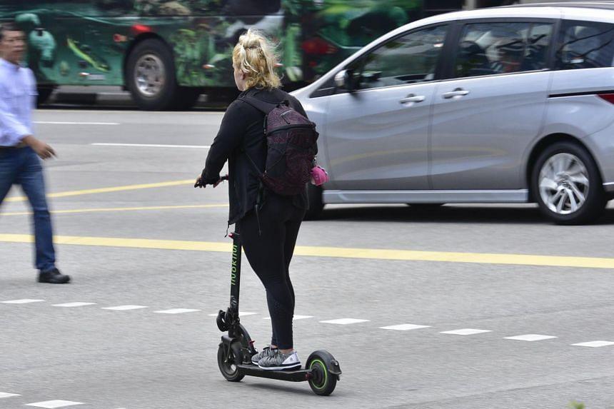 A girl rides her e-scooter along Raffles Quay.