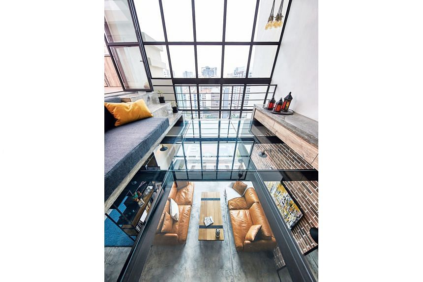 The glass-floor mezzanine creates space, but does not break the visual line of the apartment's double-volume ceiling.