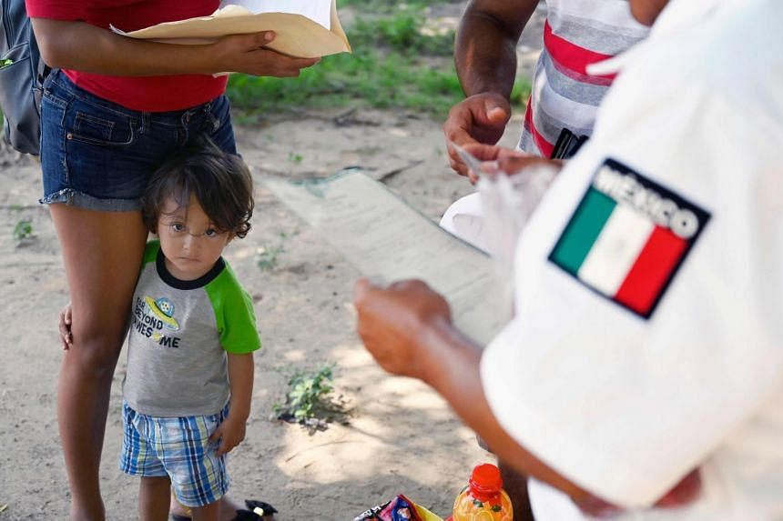 A Mexican migration officer checks identification documents of migrants from Guatemala on the banks of the Suchiate river in Mexico.