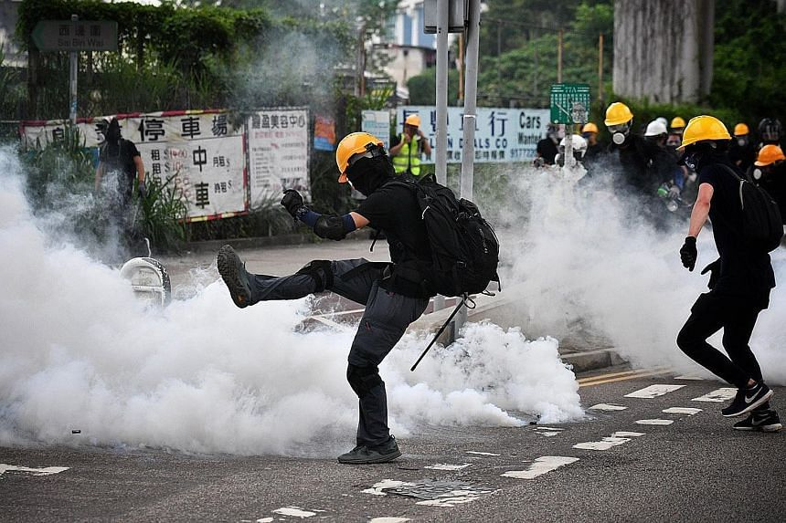 A protester berating police officers during a mass rally in Yuen Long yesterday. Protesters activating their own armed and well-protected squad of demonstrators to meet the riot police that were stationed at the village entrance near Yuen Long MTR st