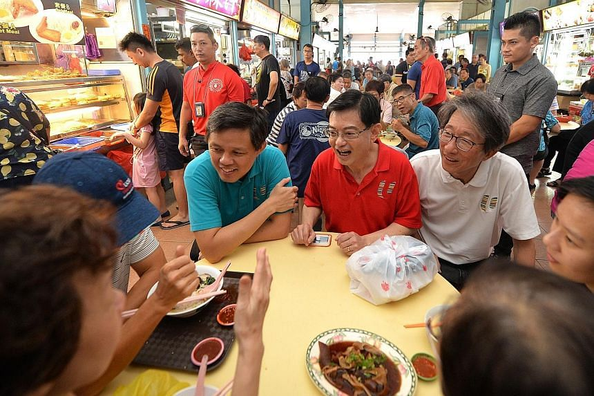 Deputy Prime Minister Heng Swee Keat, flanked by Minister for Trade and Industry Chan Chun Sing (left) and East Coast GRC MP Lim Swee Say, chatting with residents during a ministerial walkabout at The Marketplace @ 58 yesterday. It was the 40th such