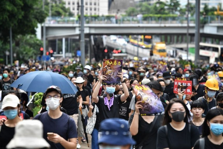 Protesters pass by the Hong Kong Police Headquarters in the district of Wanchai on July 28, 2019.