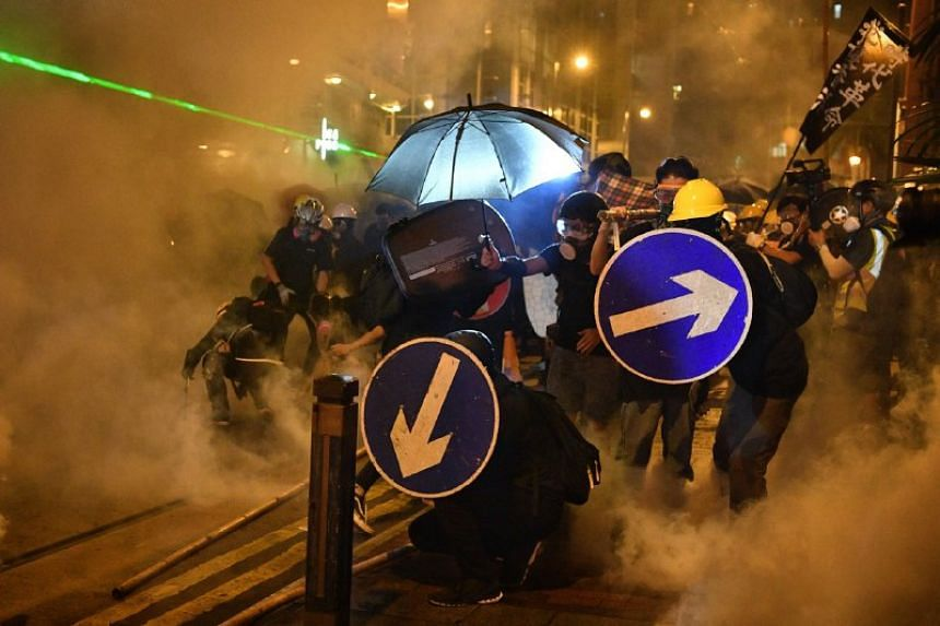 Protesters surrounded by smoke from tear gas fired by police in Sheung Wan in Hong Kong on July 28, 2019.