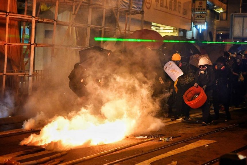 Protesters rushing to douse tear gas canisters in Sheung Wan in Hong Kong on July 28, 2019.