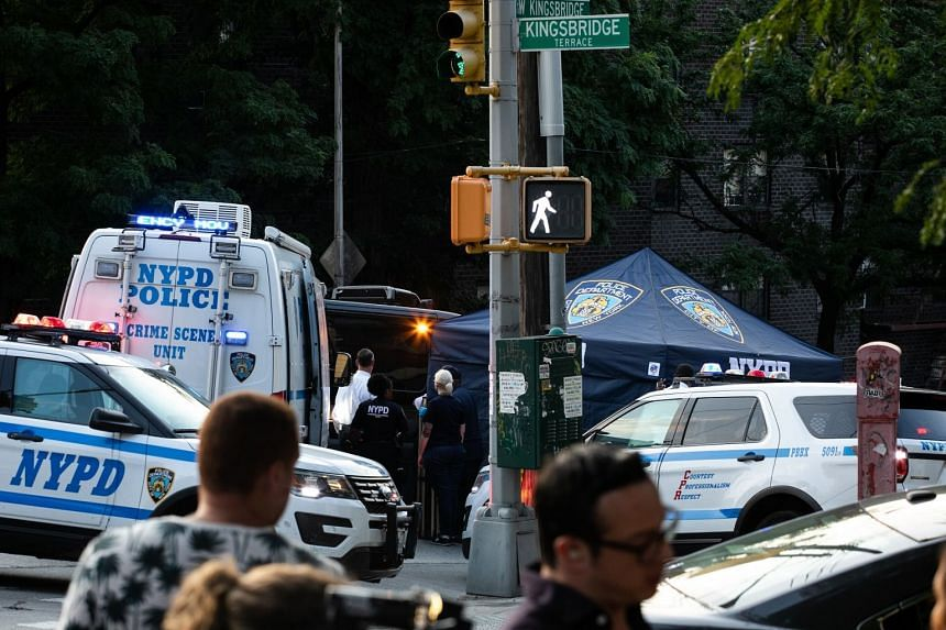 Police officers investigate an area in the Bronx where two infants were found dead in a car on Friday, July 26, 2019.