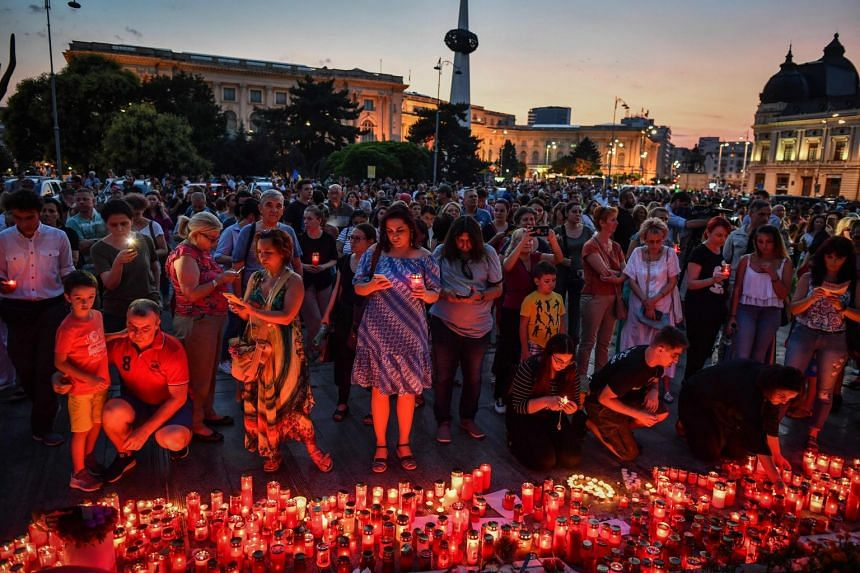 People light candles at a makeshift memorial in Bucharest to commemorate the teen.