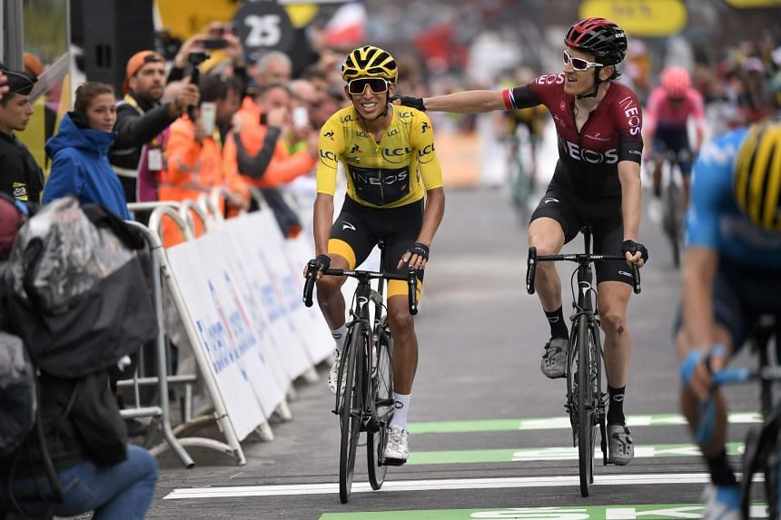 Colombia's Egan Bernal, wearing the overall leader's yellow jersey, is congratulated by Welsh teammate Geraint Thomas as he crosses the finish line of the 20th stage.