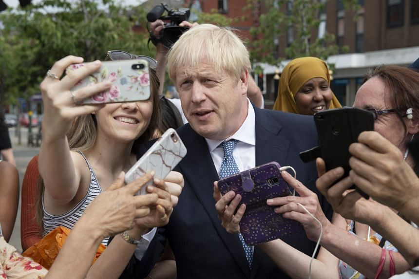 Johnson poses for selfies during a visit to Birmingham, England, after becoming prime minister.