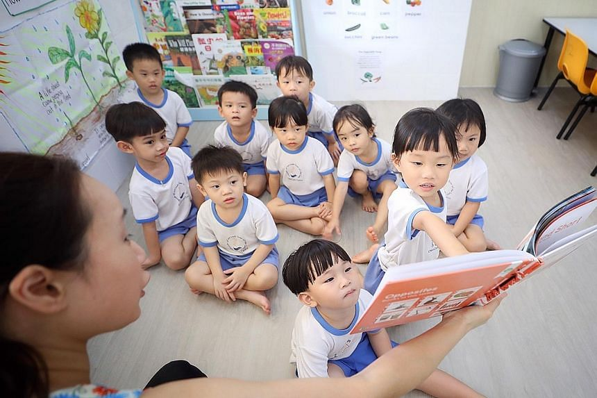 An English teacher conducting a reading lesson for children at Our Lady Star of the Sea Child Care Centre in Yishun last week.