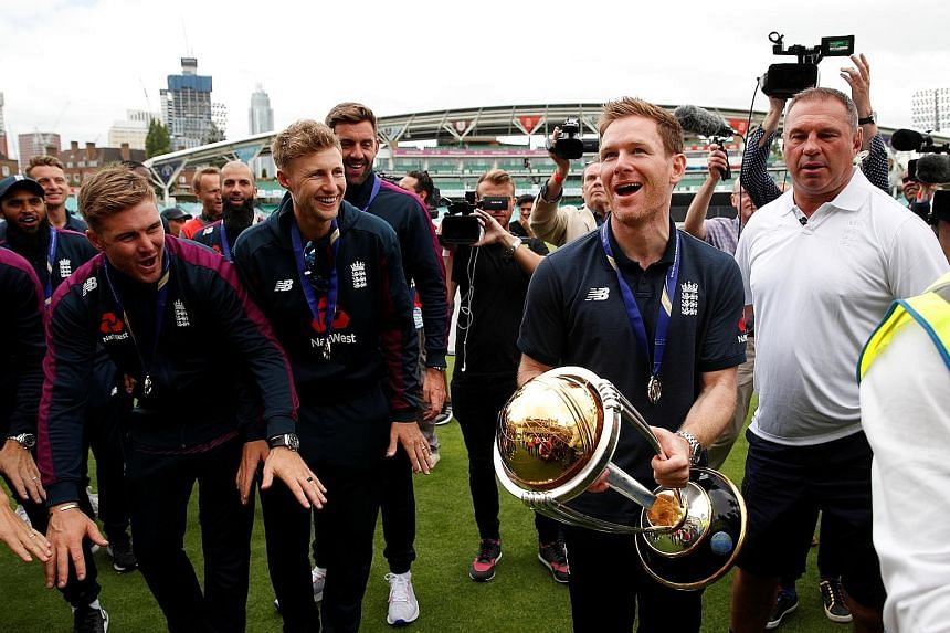 England one-day captain Eoin Morgan with the Cricket World Cup as teammates join in the celebrations at the Oval in London on July 15, a day after they edged out New Zealand in a thrilling final at Lord's.
