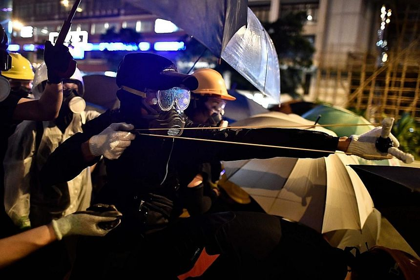 A protester using a slingshot to fire projectiles at police. Some hurled objects like bottles, rocks and umbrellas at officers, or pushed flaming objects - including rubbish bins and a metal cart - at them. PHOTO: AGENCE FRANCE-PRESSE Protesters runn