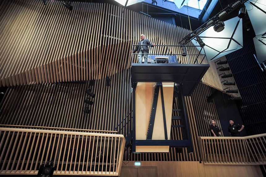 Piano builder David Klavins standing tall next to the 470i Vertical Concert Grand piano in the new concert hall in Ventspils, Latvia. The steel-framed piano hangs as if in mid-air, some three storeys above the audience. To play it, pianists must clim
