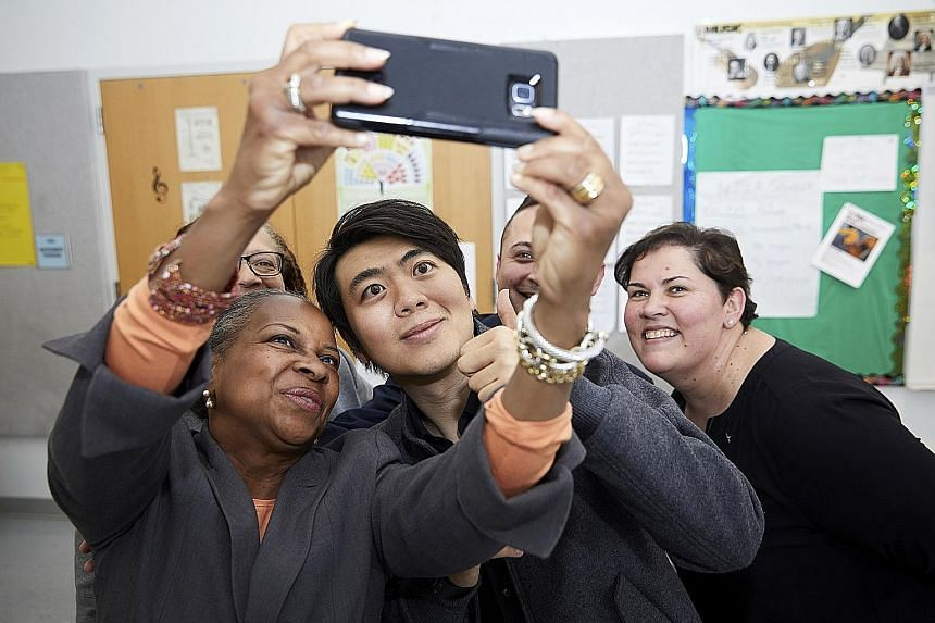 Lang Lang taking a selfie with school administrators at the opening of Lang Lang International Music Foundation's new piano lab at First Avenue Elementary School in Newark in April.