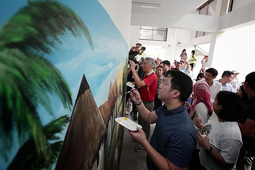 Prime Minister Lee Hsien Loong and Dr Lam Pin Min, MP for Sengkang West and adviser to the SMC's grassroots organisations, adding the finishing touches to a wall mural depicting life in the past by artist Vincent Seet yesterday. Mr Seet and fellow Ja