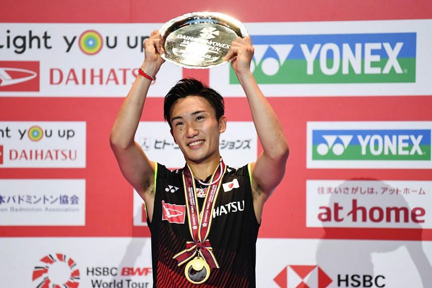 Kento Momota of Japan receive a trophy after the men's singles final match against Jonatan Christie of Indonesia at the Japan Open badminton tournament.