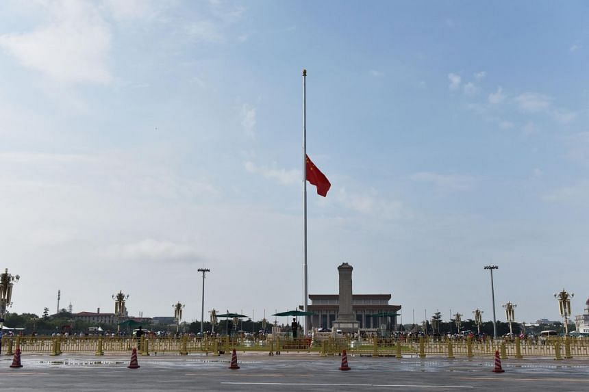 At Tiananmen, soldiers at the daily flag-raising ceremony raised the red banner to half-mast as hundreds of tourists looked on under rainy skies in the capital on July 29, 2019.