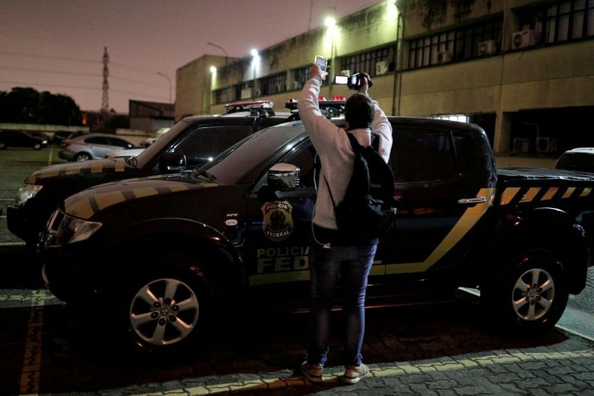 A cameraman records pickup trucks with livery resembling Brazil's federal police which were used during the theft at Guarulhos airport in Sao Paulo.