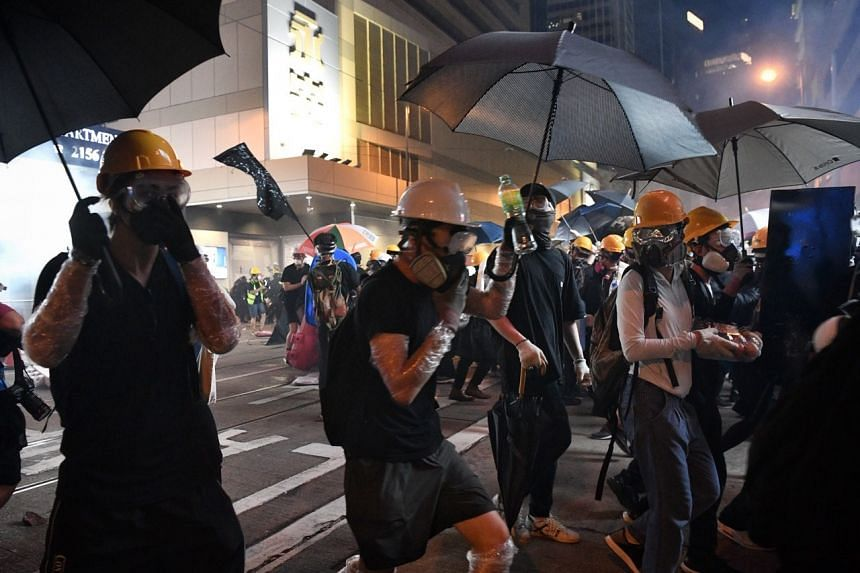 Protesters hold on to their gas masks and run.
