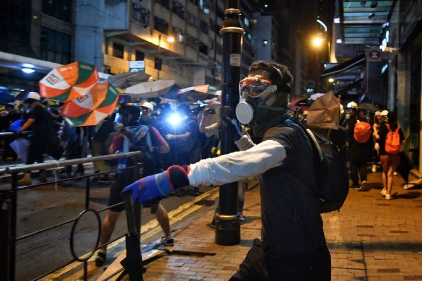 A protester throws a rock at the police in Sheung Wan in Hong Kong on July 28, 2019.