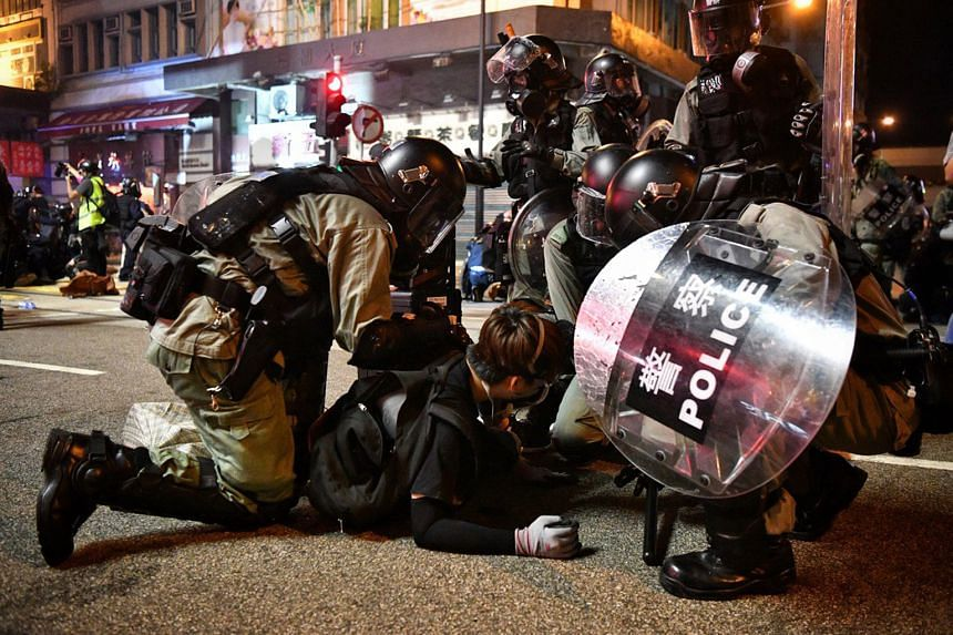 Hong Kong police arresting protesters near Morrison Street yesterday. Pitched battles between both sides raged late into the night on the western side of Hong Kong Island. The protesters set up barricades in Causeway Bay and Sheung Wan, resulting in