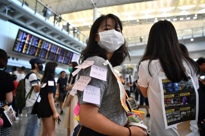 At the airport, protesters pasted signs on themselves with protest slogans and graphics explaining the recent police violence in Hong Kong.