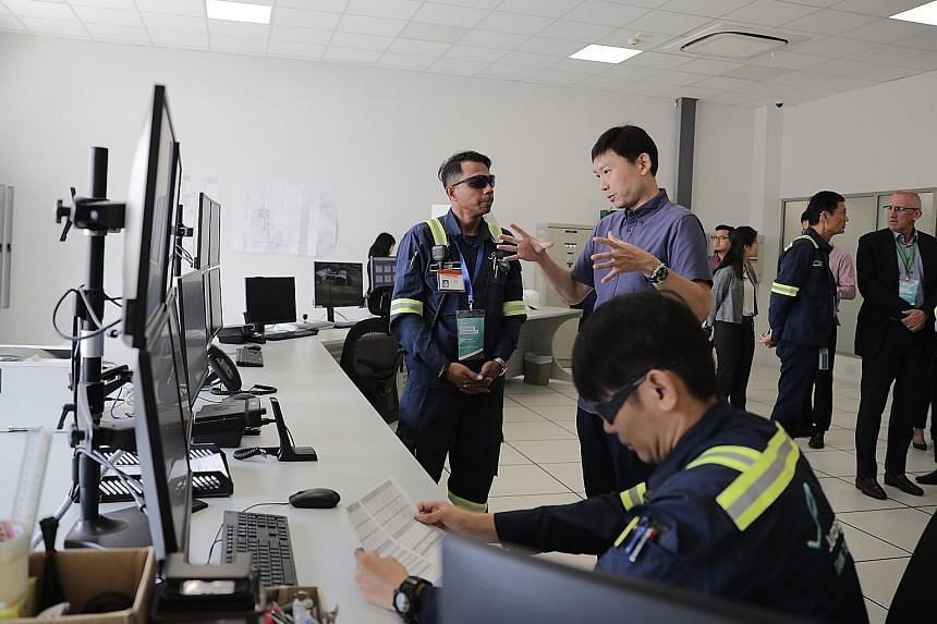 Senior Minister of State for Trade and Industry Chee Hong Tat with Jurong Port Tank Terminals shift leader Yusoff Khan in the central control room of the newly opened port yesterday.