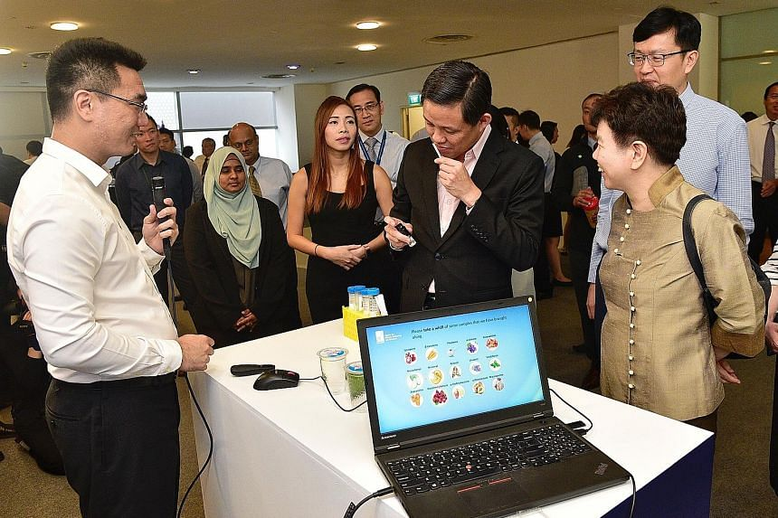 Research fellow and former A*Star scholarship recipient Andy Ng Yao Zong (left) watching as Trade and Industry Minister Chan Chun Sing takes a whiff of a fragrance produced by bio-engineered yeast cells. With them are (from right) A*Star chairman Cha
