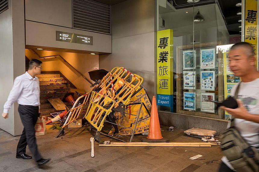 Barriers and other street objects used by demonstrators at the bottom of a pedestrian overpass yesterday morning, after clashes between protesters and the police in the Sheung Wan area on Sunday. PHOTO: BLOOMBERG