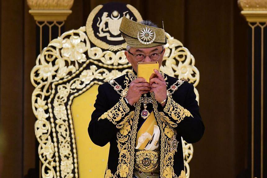 Sultan Abdullah Ri'ayatuddin kissing a copy of the Quran during his royal coronation at the National Palace in Kuala Lumpur, on July 30, 2019.