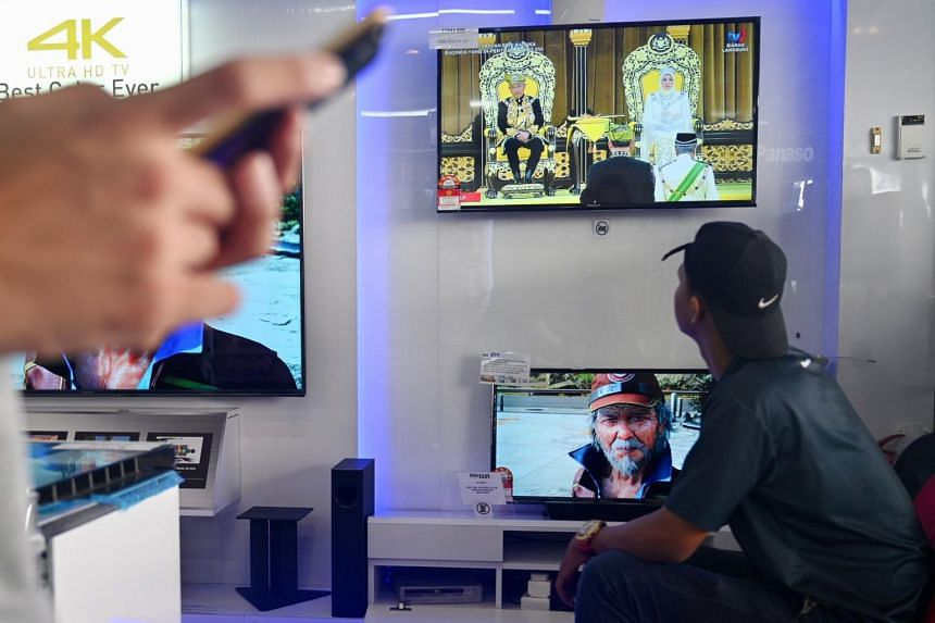 A man watches a live television broadcast of the royal coronation of Malaysia's new Sultan Abdullah Ri'ayatuddin in a shop in Kuala Lumpur on July 30, 2019.