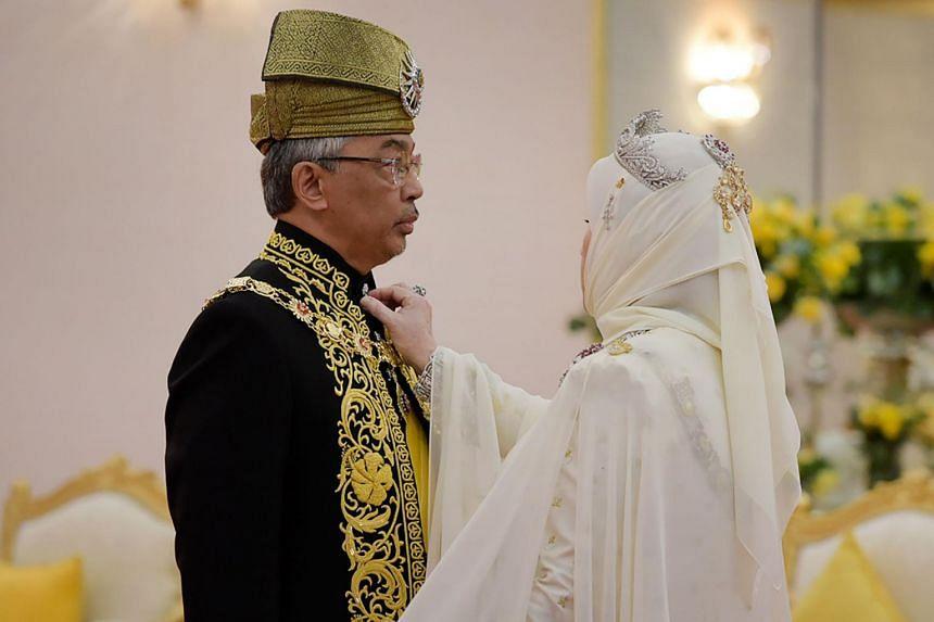 Queen Tunku Azizah Aminah Maimunah Iskandariah Sultan Iskandar adjusts Sultan Abdullah Ri'ayatuddin outfit during his royal coronation at the National Palace in Kuala Lumpur on July 30, 2019.