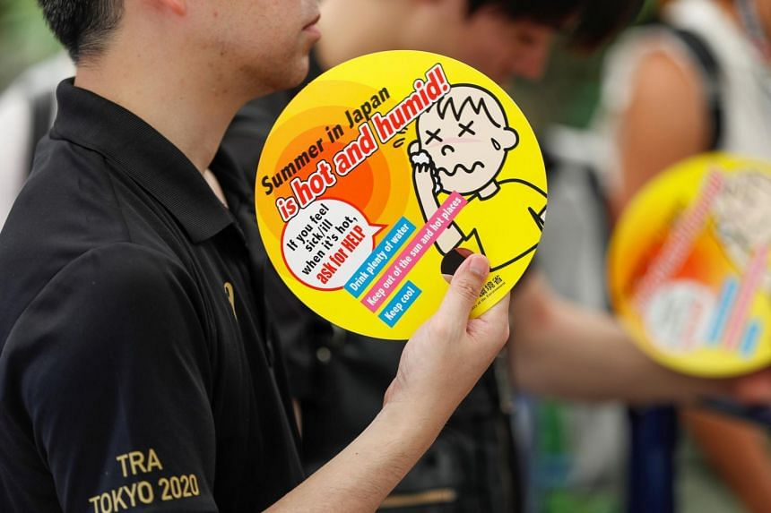 Visitors use paper fans featuring attention-seeking messages during a proving test held on on July 26, 2019 to test heat countermeasures in preparation for the upcoming Tokyo 2020 Olympic and Paralympic Games.
