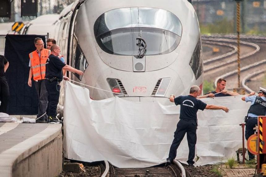 Policemen and fireworkers hold a white blanket as a visual cover at the site of a deadly attack at the railway station in Frankfurt am Main, on July 29, 2019.