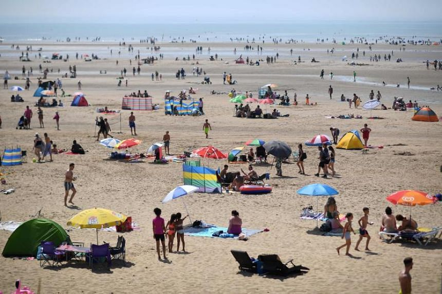 Beach-goers enjoy the sunshine by the sea in Camber Sands, southern England, during a heatwave in Britain.