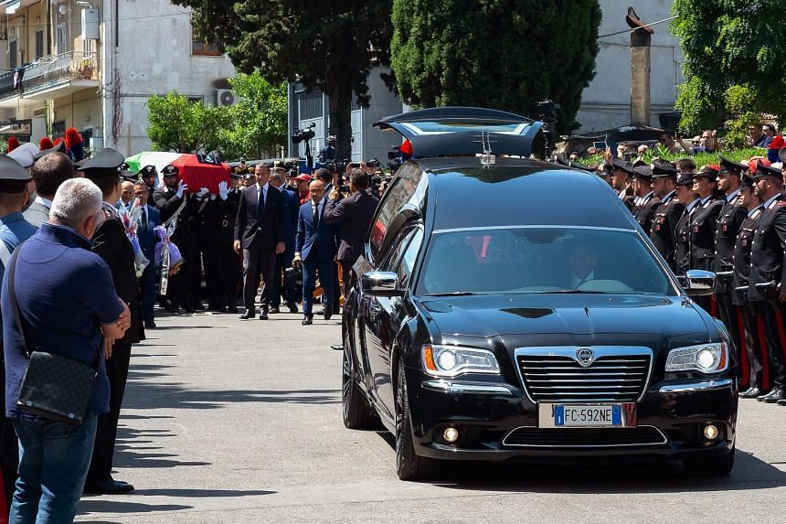 Carabinieri officers and people look on as the coffin of Mario Cerciello Rega arrives for the funeral mass.