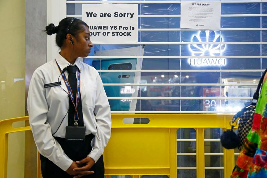 A security officer stands guard outside a closed Huawei store.