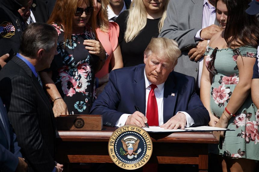 US President Donald Trump, with 9/11 first responders and family members, at a signing ceremony for H.R. 1327, an act to permanently authorise the Sept 11 victim compensation fund in the Rose Garden of the White House on July 29, 2019.