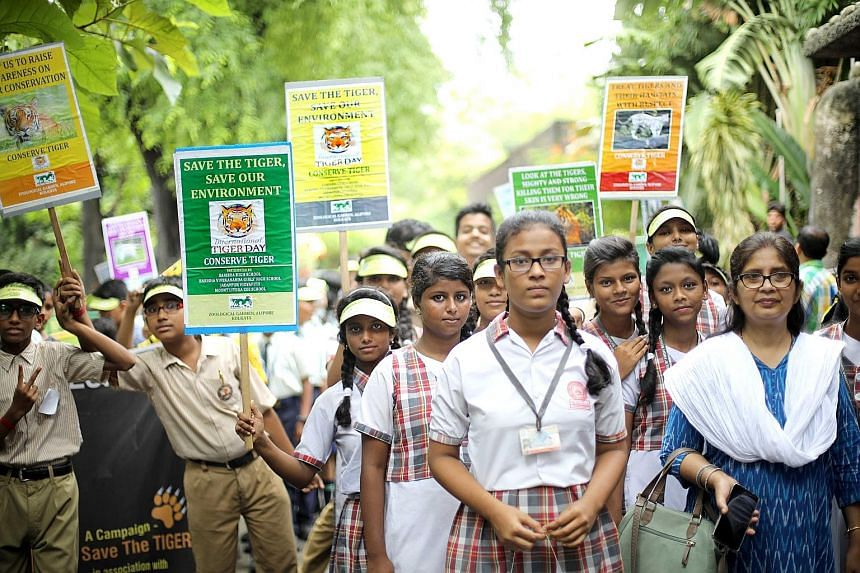 Indian students holding posters of the Bengal tiger during a march on World Tiger Day at the Alipore Zoo in Kolkata on Monday. PHOTO: EPA-EFE