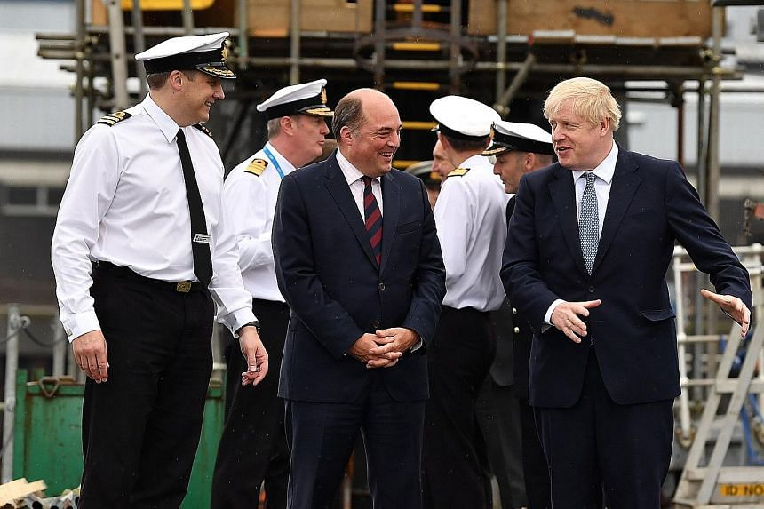From left: Commander Justin Codd with Britain's Defence Secretary Ben Wallace and Prime Minister Boris Johnson aboard the submarine, HMS Victorious, during a visit to Scotland on Monday.