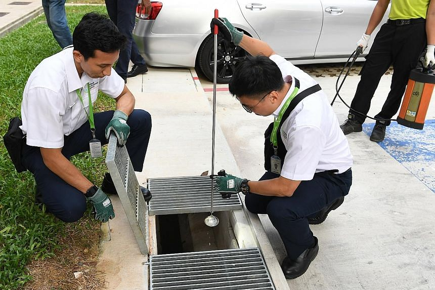 Officers from the National Environment Agency checking for mosquito larvae in Woodlands. As of July 20, nine people in Singapore, including a 46-year-old man, have died from dengue this year. ST PHOTO: KHALID BABA