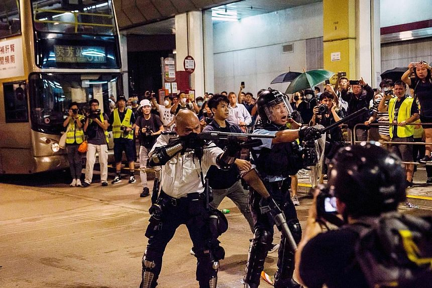 Police officers in a clash with protesters outside the Kwai Chung Police Station last night. They used pepper spray and batons in a bid to disperse the protesters. PHOTO: AGENCE FRANCE-PRESSE