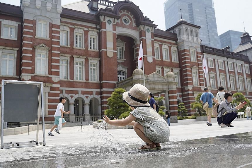 A child playing with water in front of the Tokyo Station building on Monday. Tokyo is likely to see daytime highs of 34 deg C this week. PHOTO: BLOOMBERG