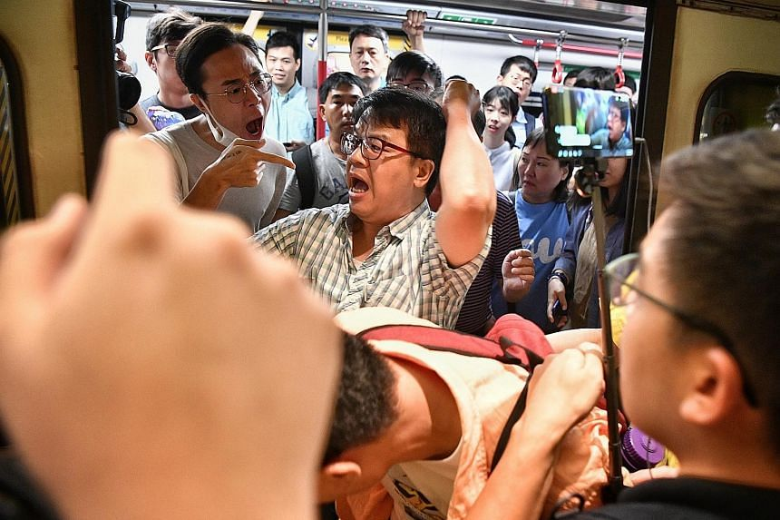 Police officers at Tiu Keng Leng Station during the disruption of train services yesterday. Tempers flared at the various affected stations and the police were called, but no arrests were made. An angry passenger (centre) who elbowed a protester out