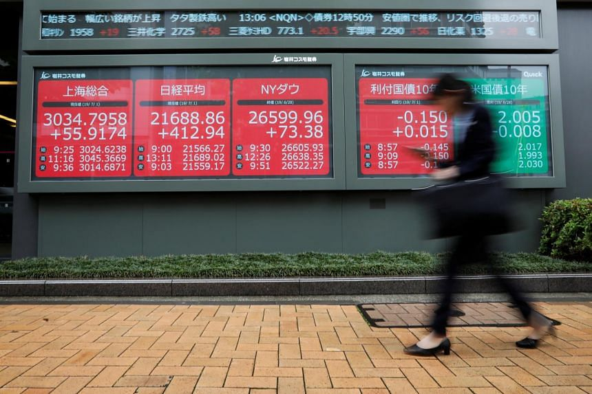 A woman walks past an electric screen showing world markets indices outside a brokerage in Tokyo, Japan, on July 1, 2019.
