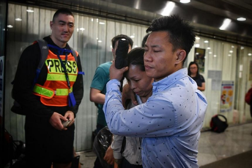 A man tries to shield a woman from the media as they exit the Eastern Magistrates' Court in Hong Kong on July 31, 2019. The woman was one of those arrested during the protests over the weekend.