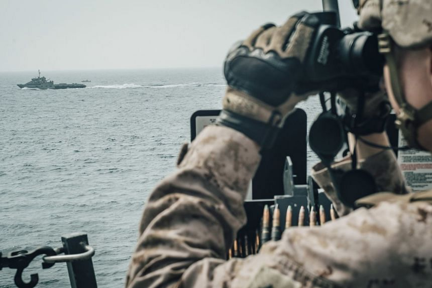 A US Marine observes Iranian fast attack craft from aboard the USS John P. Murtha during a Strait of Hormuz transit.