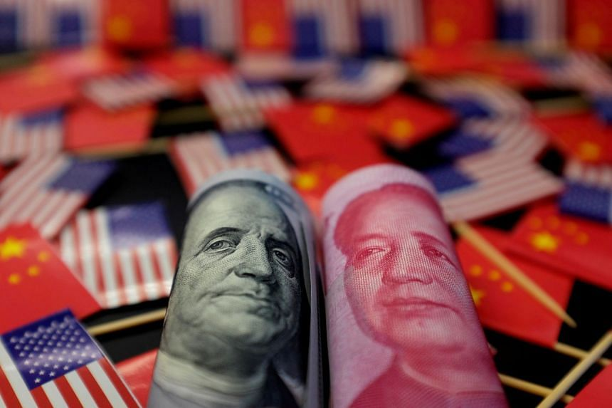 A US dollar banknote and a Chinese yuan banknote are seen among US and Chinese flags in this illustration picture.